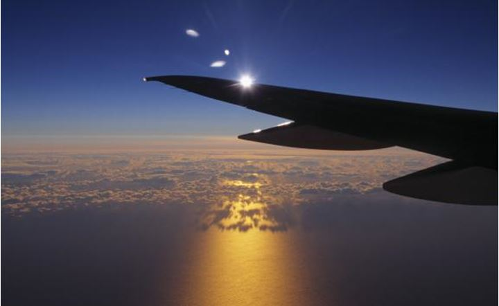 An airplane wing above sea with clear blue sky and sun behind. Iceland