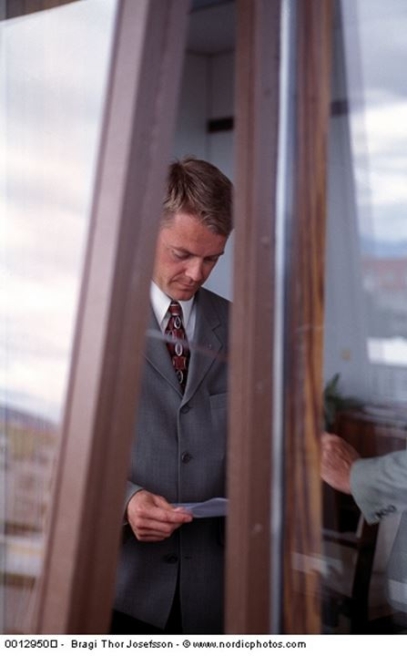 Looking through a window at two business men in an office. Iceland