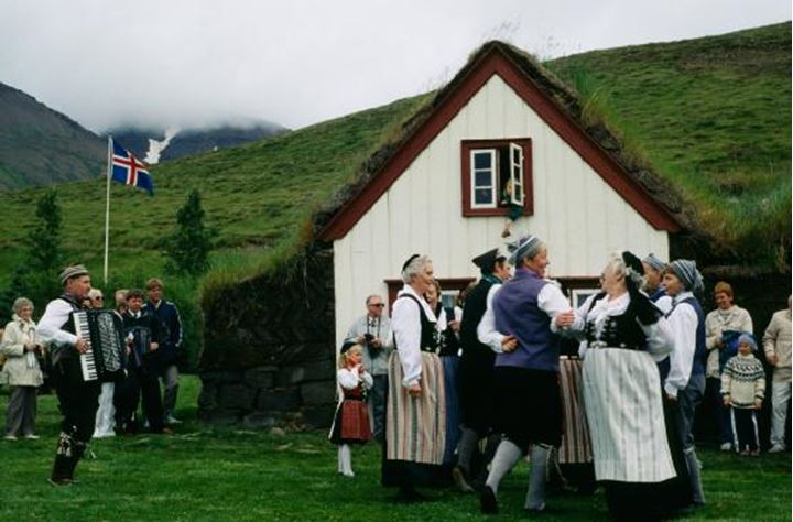 People wearing Icelandic national costumes,dancing folk dance infront of a turfhouse