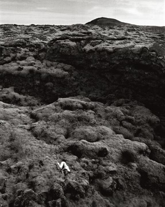 High angle view of a naked person lying in a mossy lava field, Reykjane, Iceland