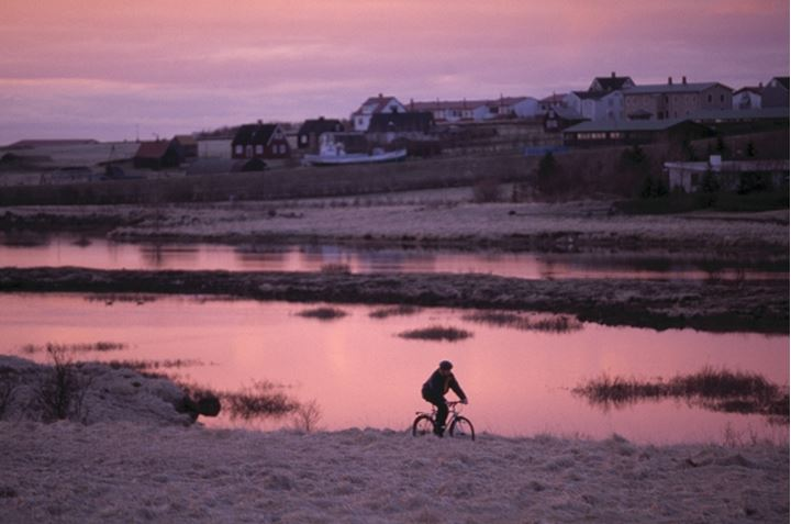 Person riding a bike by a river and houses of a folk museum on the other side, Reykjavik, Iceland