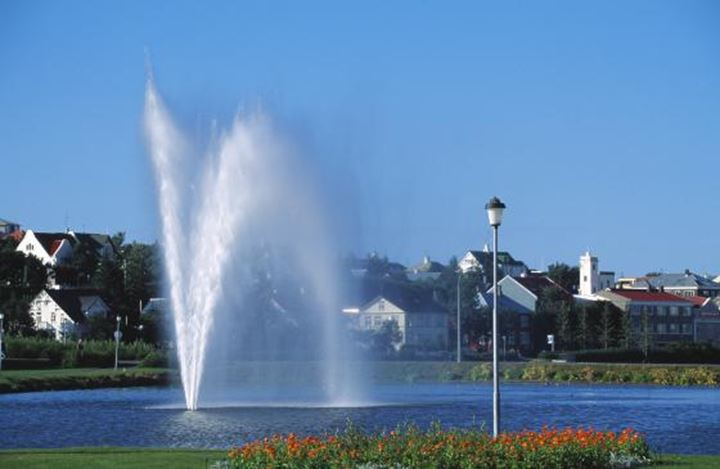 Pond and fountain in Reykjavik, houses and trees behind