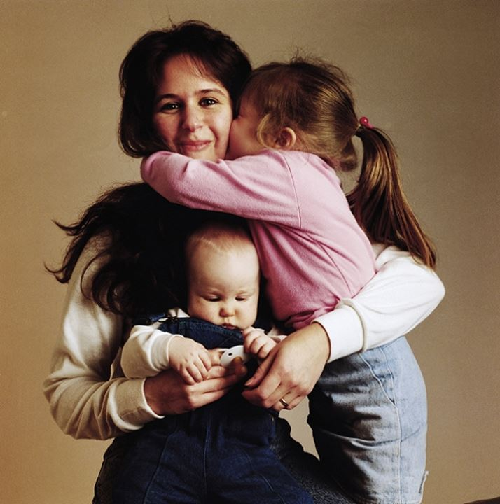 Mother being kissed and hugged by her young daughter with baby son in her arms