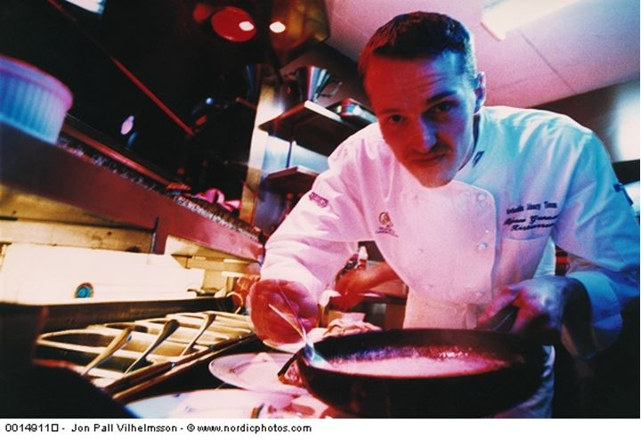 Chef in kitchen holding a frying pan and looking at camera