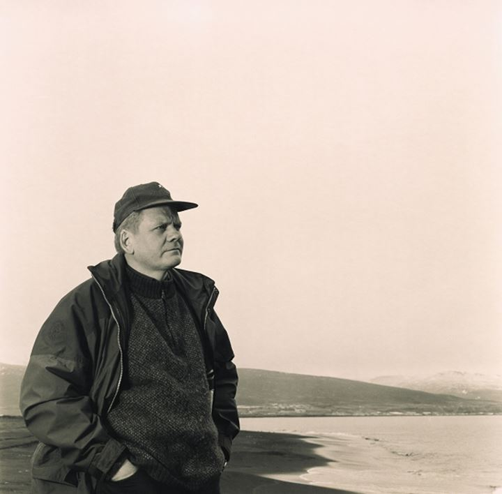 Man with a cap standing at the beach, looking out to sea