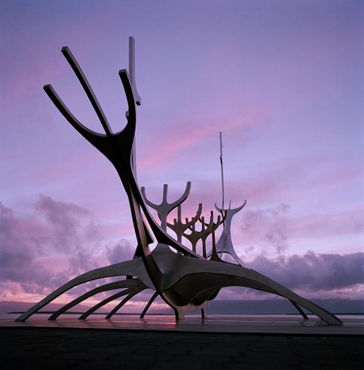 Metal sculpture by the sea in Reykjavik and purple sky of sunset in background
