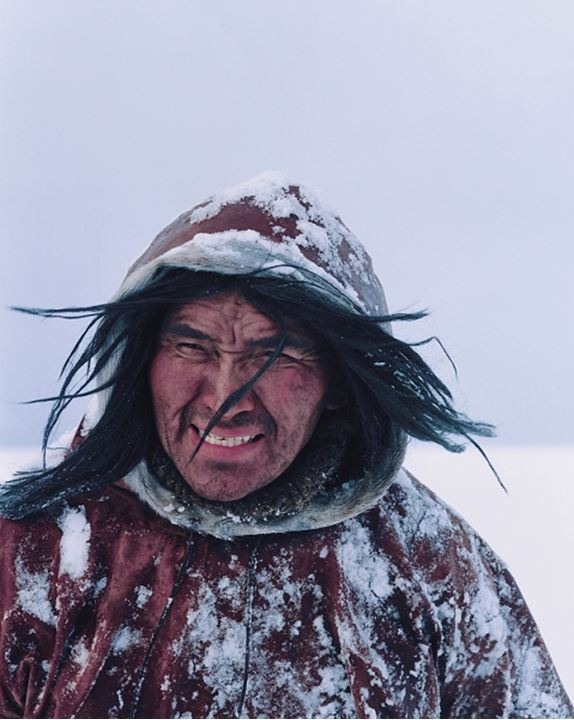 Eskimo man in a winter coat in the snow, long hair blowing in wind