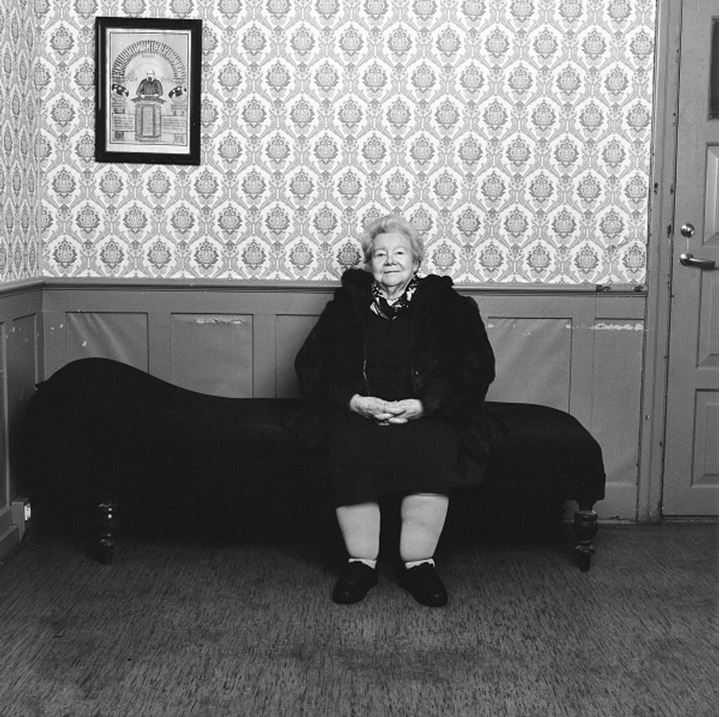 Mature woman in winter coat sitting on a sofa, picture on wall behind