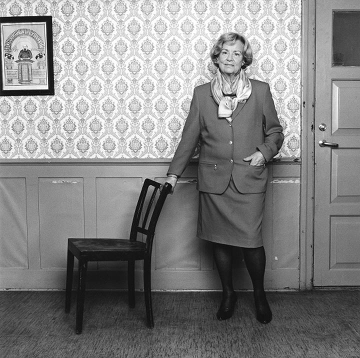 Mature woman wearing skirt, jacket and high heels leaning to a chair, wall behind her