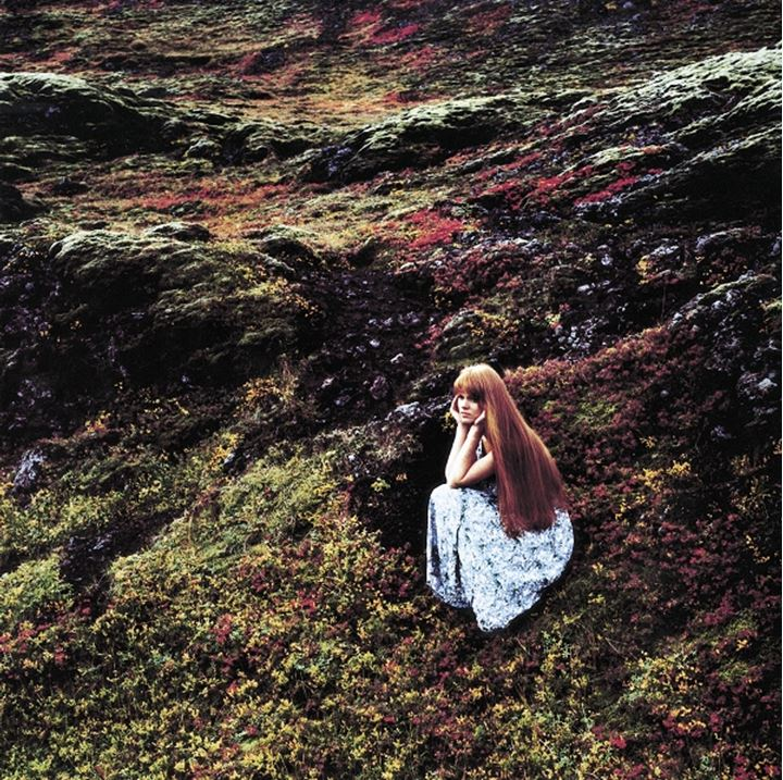 Woman with long hair wearing a dress, sitting in a mossy lava field, resting head in hands, Iceland