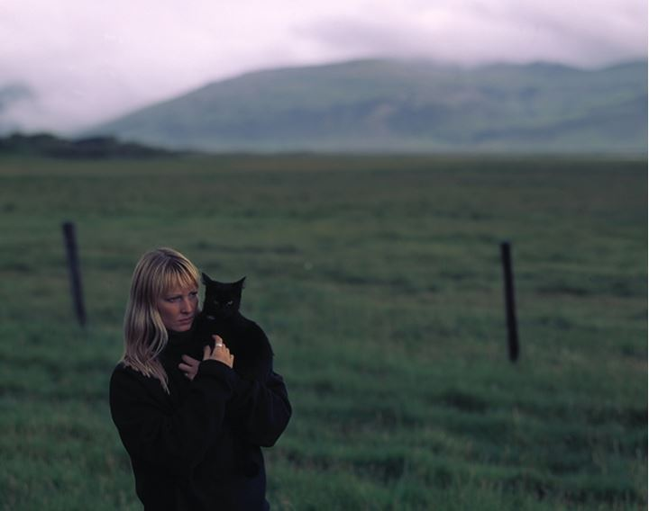 Woman with blond, long hair holding a black cat, landscape behind