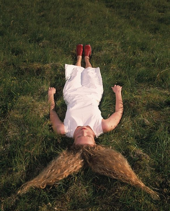 Young woman wearing white dress, with long, blond hair, lying in grass