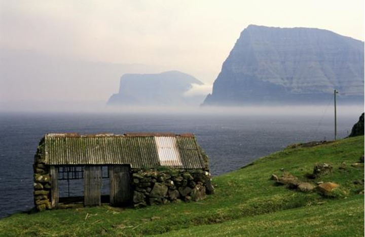 An old hut in Faroe Islands, ocean and mountains in background