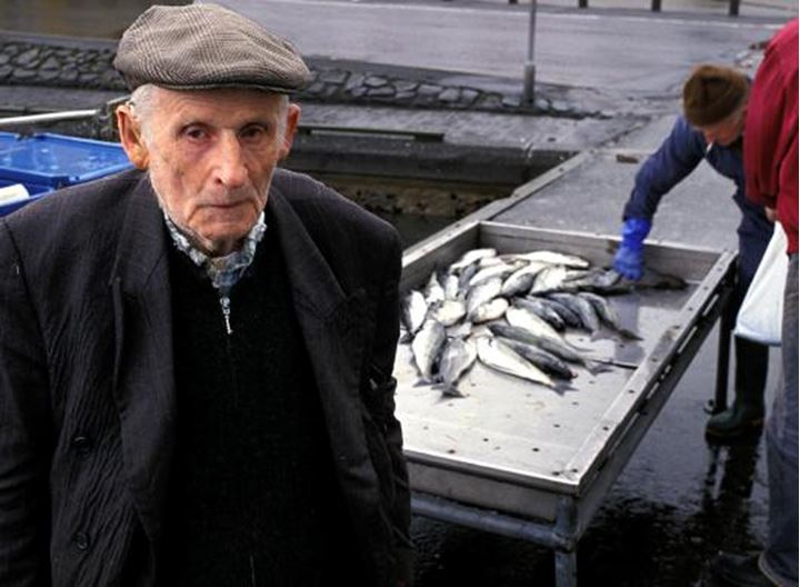 An old man wearing a hat, men working with fish behind him