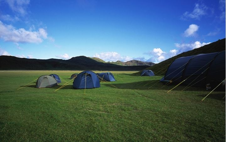 Iceland - Camping tents in a grass field with mountains in the background