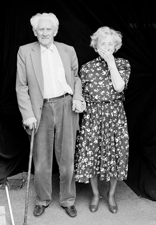Old couple standing and looking at camera, woman wearing dress and man with a stick