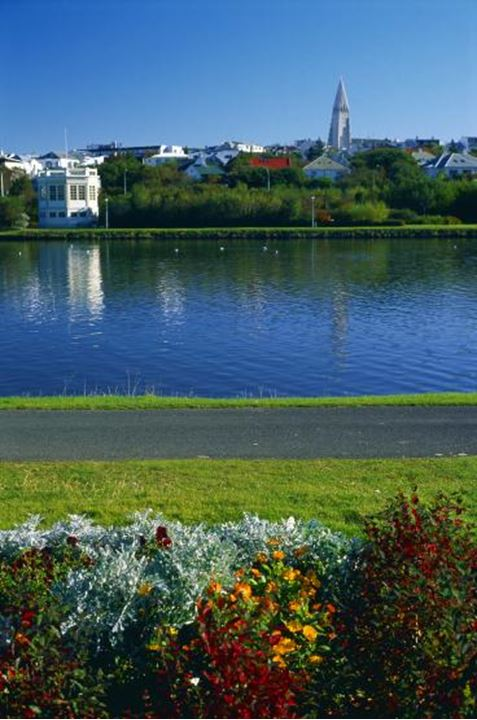 The pond in Reykjavik, Reykjavikurtjorn, green grass, flowers, houses and and a churchtower in distance