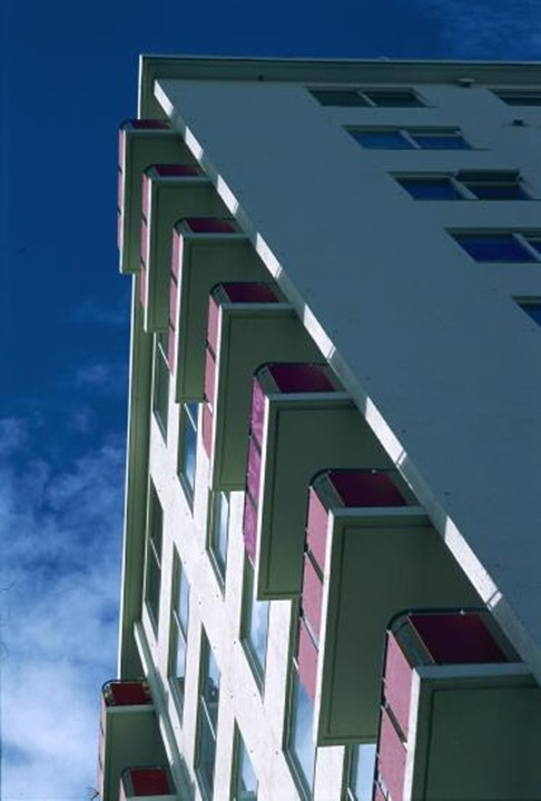 Looking up at an apartment building under a partly clouded sky