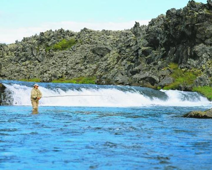 Man standing in a river, fly fishing