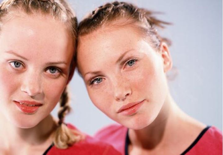 Two young women standing close together and looking at camera