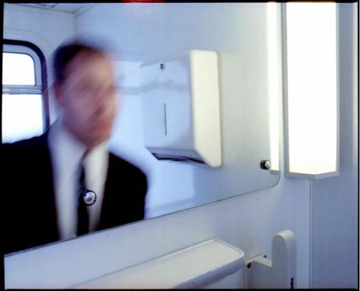 Blurred reflection of a buisness man in a lavatory mirror