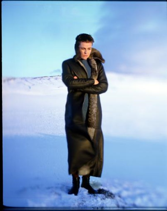 Woman wearing a wintercoat standing in snow with folded arms