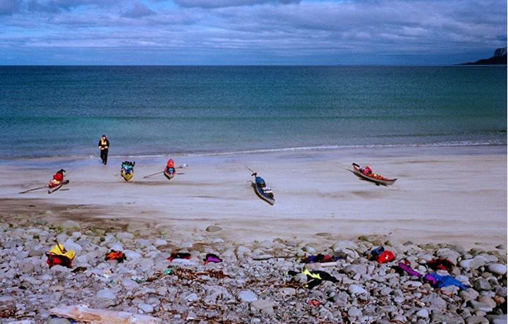 Five kayaks and one person on a beach