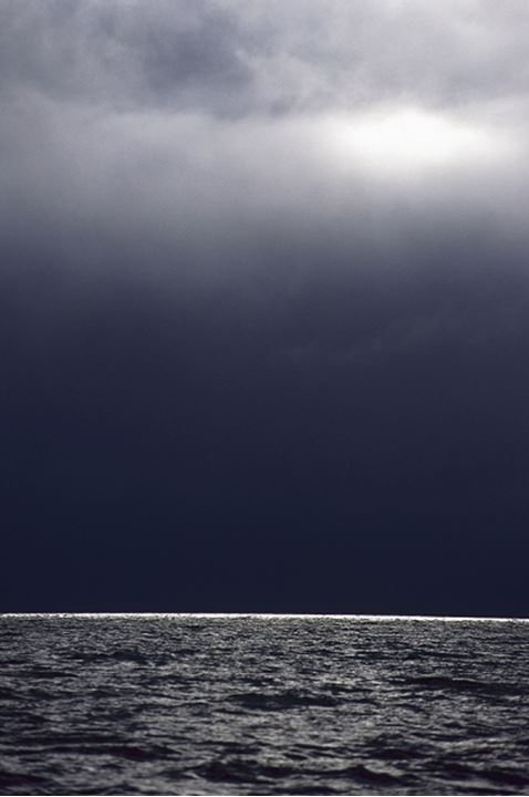 Dark clouds in an eerie sky, ocean at horizon beneath