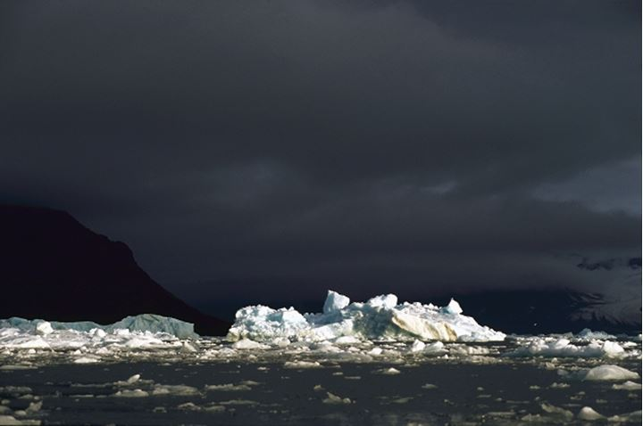 Ice floating on sea, dark sky in background