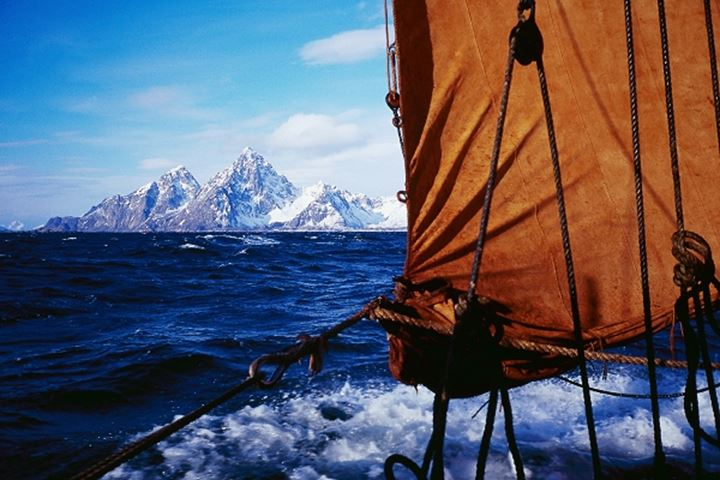 A sail and some ropes of an old ship sailing, mountains in background