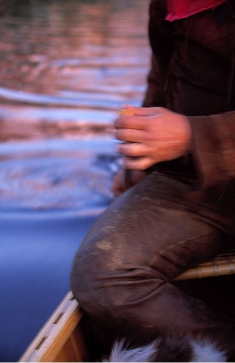 Mid section view of a man sitting in a boat