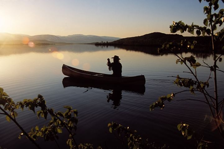Silhouette of a person sailing a canoe in a lake
