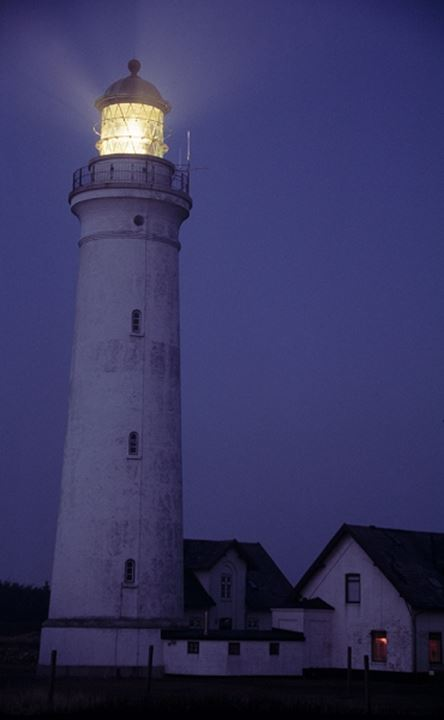 Lighthouse beacons lit up at night