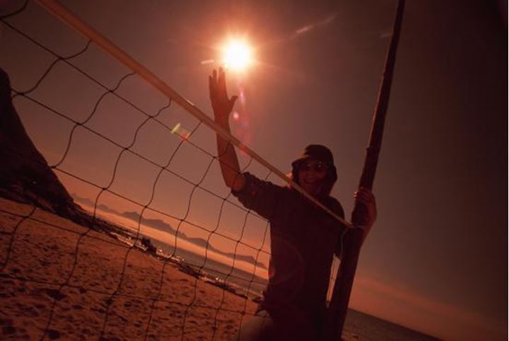A man reaching out his hand by a volleyball net, sun and landscape behind