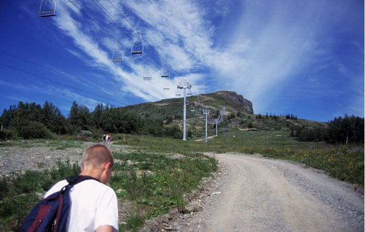 People walking up a gravel road at summertime, a ski lift above them.