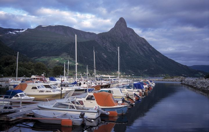 A pier with little boats, mountain in the background.