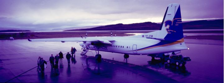Passengers walking away from an airplane on a runway, Egilsstadir, Iceland, landscape in background.