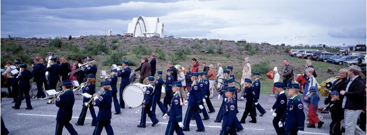 Scouts paradeing in Kópavogur town, Kópavogschurch  in background
