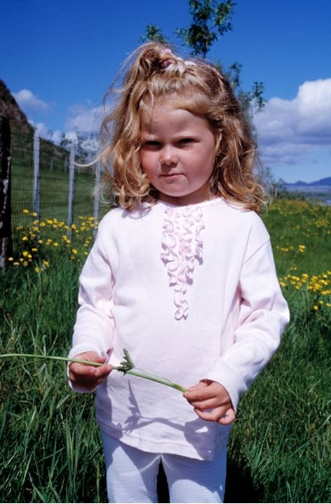 Portrait of a little blonde girl in a grass field with buttercups. Iceland