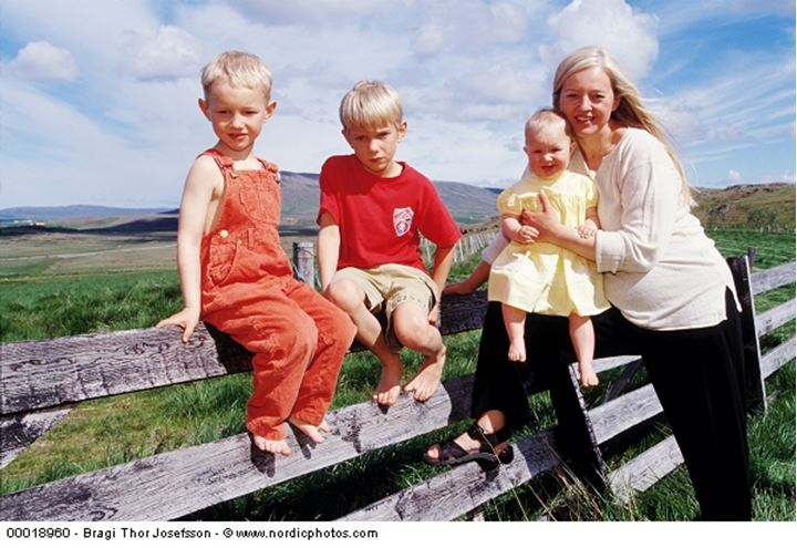 A woman and her children sitting on a wooden fence on sunny summer day