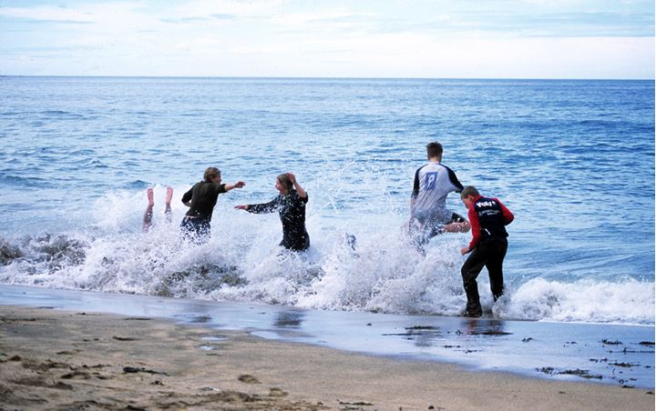People playing and splashing in the sea by a yellow sanded beach