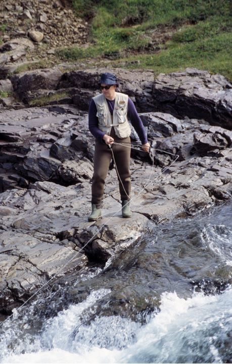 A man by a river holding a fly rod and a net