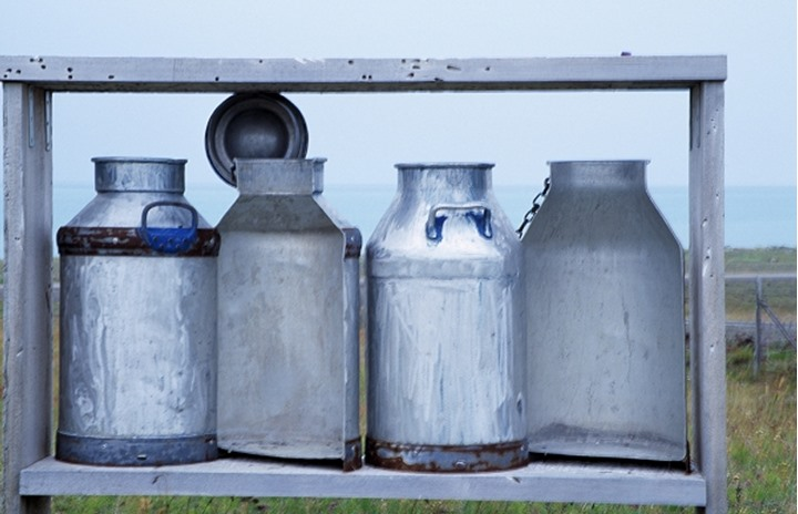 Four milk canisters on a rack