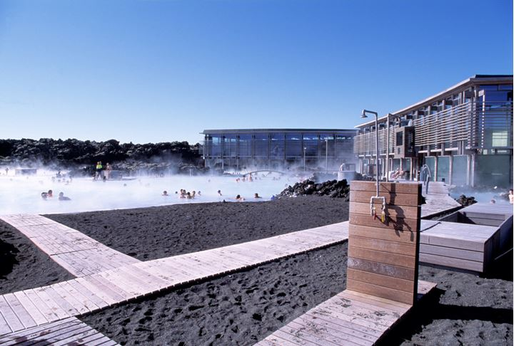 An outdoor shower at the Blue lagoon, the main building behind it and people relaxing in the lagoon.