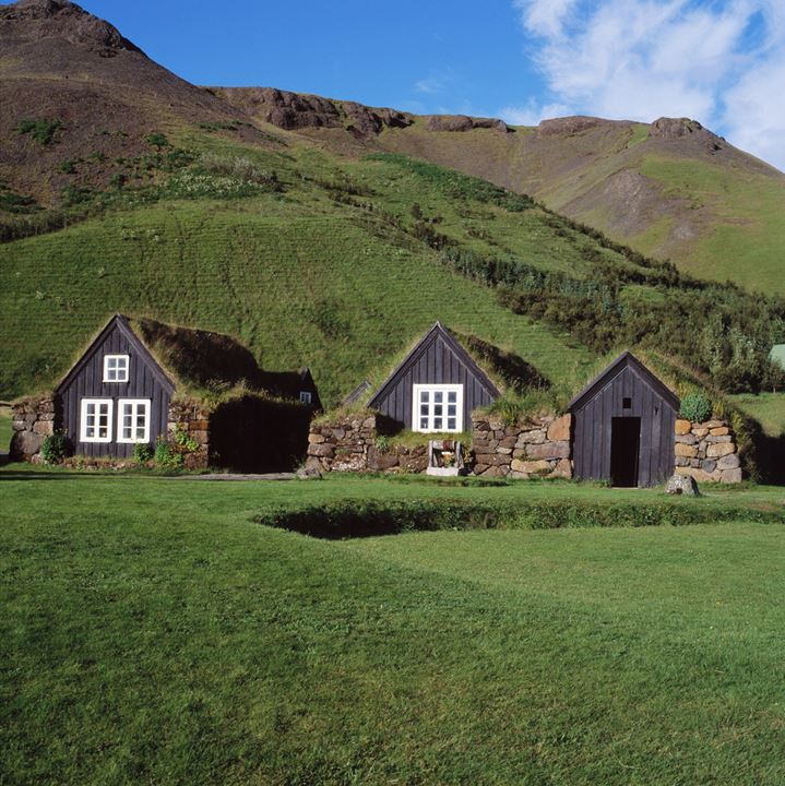Turf house in the countryside, mountain in the background.