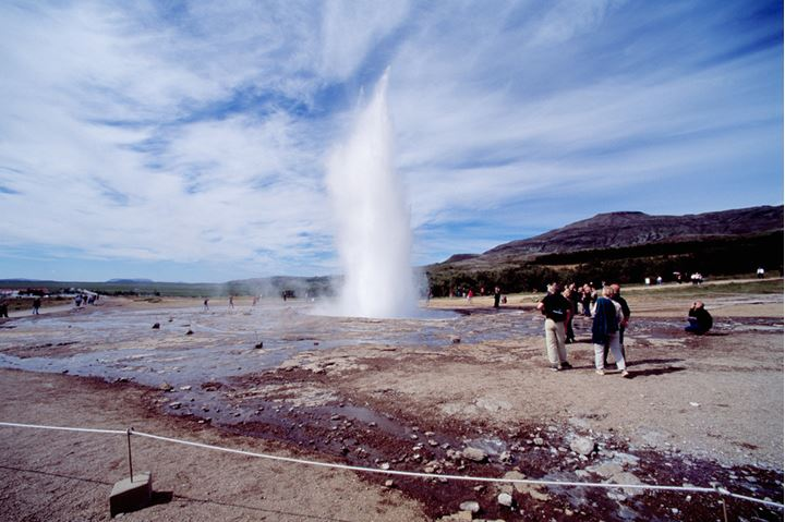 Group of people watching a geyser erupt.
