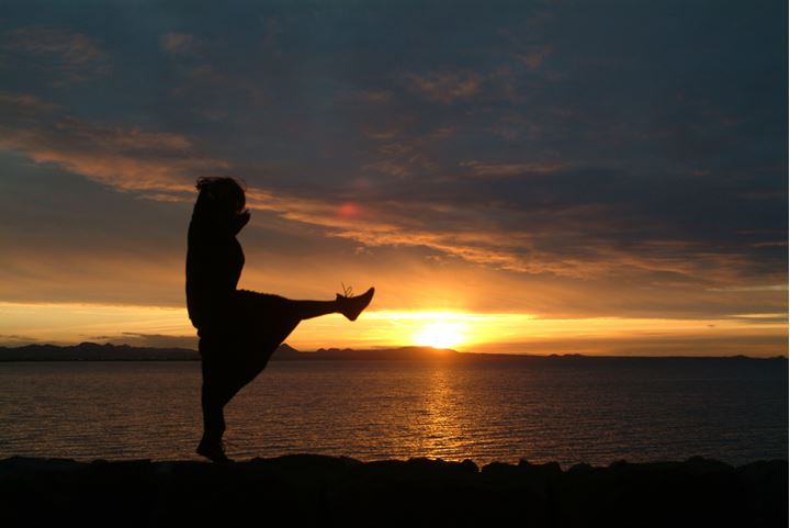 Woman jumping around in the seashore at sunset.