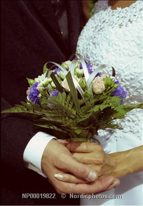Married couple holding a bouquet in there hands. Skogstorp. Sweden