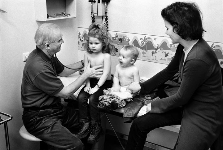 A doctor examining a little girl and her baby sibling, their mother watching