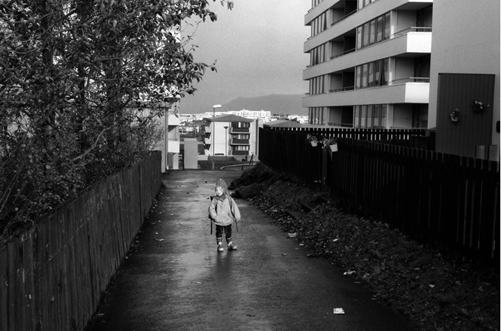 A child carrying a schoolbag, standing on a footpath and looking at camera in Kopavogur, Iceland